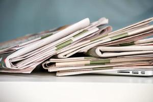 Stapel Zeitungen, auf einen Laptop gelegt foto