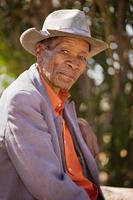 Porträt eines älteren Mannes in einem alten Hut, der draußen sitzt foto