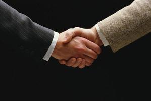 Handschlag - Hand, die auf schwarzem Hintergrund hält foto