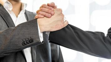 zwei Geschäftsleute greifen erfolgreich nach ihren Händen foto