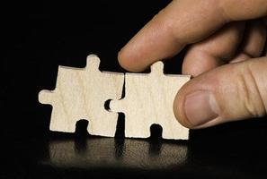 Holzpuzzle auf schwarzem Hintergrund. Nahansicht