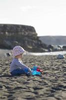 Kleinkind spielt mit Schaufel am Strand