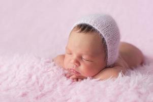 Neugeborenes Mädchen, das eine rosa gestrickte Haube trägt foto