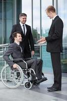 behinderter Geschäftsmann im Gespräch mit seinen Mitarbeitern foto
