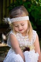 kleines Mädchen, das altmodisches Outfit herabschaut foto