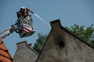 Feuerwehrmann, der verbranntes Haus dämpft foto