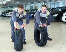 zwei Servicetechniker Automechaniker mit zwei Reifen