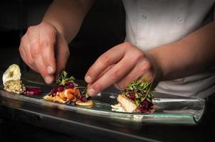 Koch bereitet eine Mahlzeit zu foto