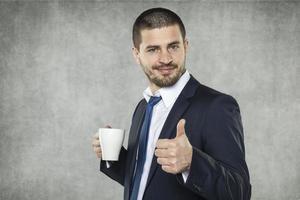 lächelnder Geschäftsmann empfehlen Kaffee foto
