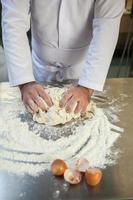 Nahaufnahme des Bäckers, der Teig knetet foto