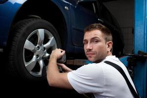Mechaniker wechselt das Rad foto