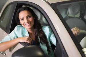 lächelnde Frau, die am Steuer ihres neuen Autos sitzt foto