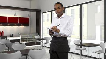 professioneller schwarzer Kellner, der Bestellungen in einem Restaurant entgegennimmt foto