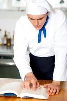 männlicher Koch unter Bezugnahme auf Kochhandbuch foto