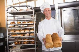 lächelnder Bäcker, der Brote zeigt foto