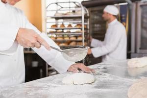Bäcker sieben Mehl auf den Teig foto