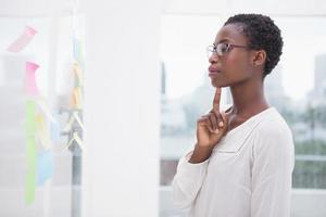 nachdenkliche Geschäftsfrau, die Haftnotizen auf Fenster betrachtet