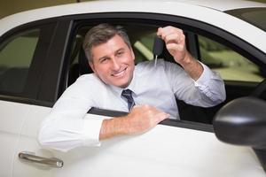 lächelnder Mann, der Schlüssel hält, der in seinem Auto sitzt foto