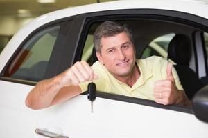 positiver Kunde, der einen Schlüssel hält, der in seinem Auto sitzt