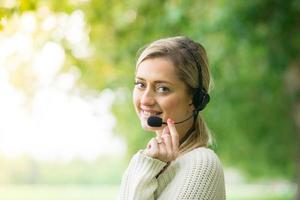 Geschäftsfrau, die mit ihrem Headset im Park spricht foto