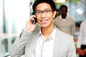 glücklicher Geschäftsmann, der auf dem Smartphone spricht