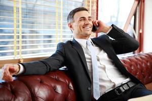 Geschäftsmann sitzt und telefoniert foto