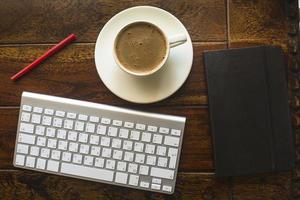 Tastatur, schwarzes Notizbuch mit Bleistift und eine Tasse Kaffee