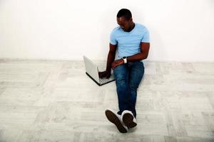 Porträt des afrikanischen Mannes, der auf dem Boden sitzt foto