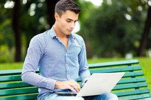 junger Mann mit einem Laptop im Freien foto