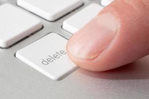 Finger drücken eine Löschtaste foto