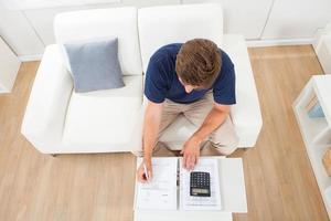 Mann, der Hausfinanzen am Tisch berechnet foto