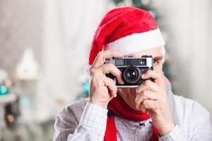 älterer Mann, der Foto auf Weihnachtshintergrund nimmt