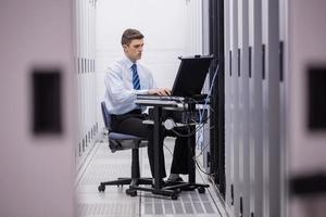 Techniker sitzt auf Drehstuhl mit Laptop zur Diagnose von Servern foto