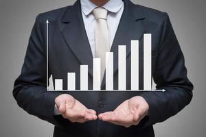 Geschäftsmann stehende Haltungshand, die Graphfinanzierung isoliert hält foto