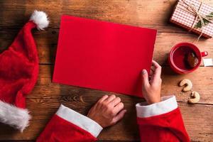 Weihnachtsmann und Wunschliste foto