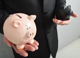 Geschäftsmann mit Sparschweinen