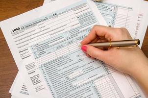 Frauenhand, die Einkommensteuerformulare 1040 ausfüllt foto