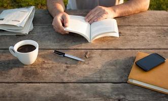 Mann, der ein Buch auf Holztisch liest foto