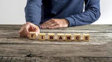 Mann im blauen Hemd, das das Wort Finanzen zusammenbaut foto