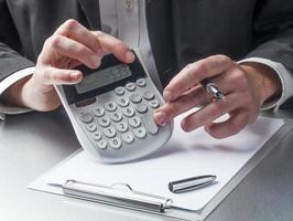 Geschäftsmann Hände, die sich um Finanzen mit Taschenrechner kümmern