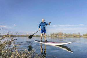 älterer Mann auf sup Paddleboard foto