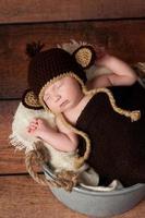 Neugeborenes, das einen Affenhut trägt foto