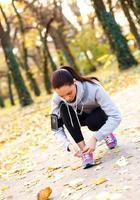 Läufer bindet Schnürsenkel und hört Musik. foto