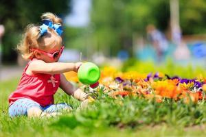 kleines Mädchen, das Blumen im Sommer gießt foto