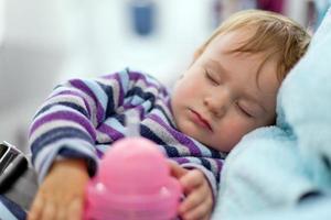 Mutter und schlafendes Baby reisen im Flugzeug foto