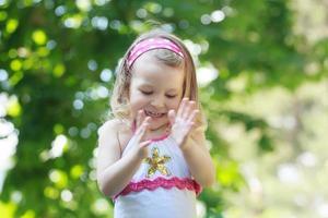 glückliches lockiges Kleinkindmädchen, das mit ihren Handflächen klatscht foto