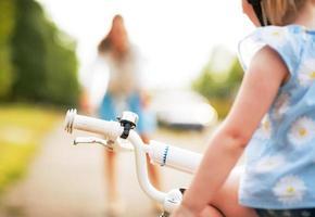 Baby, das auf Fahrrad und Mutter im Hintergrund sitzt. Nahansicht foto