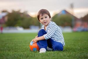 kleiner Kleinkindjunge, der Fußball und Fußball spielt und Spaß übertrifft