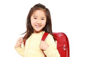 japanisches Schulmädchen mit rotem Schulranzenlächeln foto