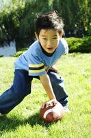junger asiatischer Junge, der Fußball spielt